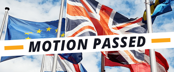 UK and EU flags fly in the wind, with a banner on top reading 'motion passed'